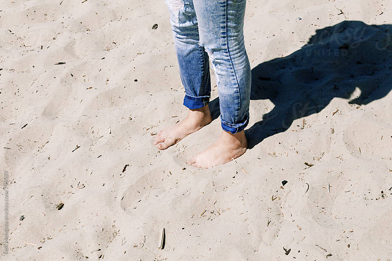Feet in the sand.  by Neil Mendoza for Stocksy United