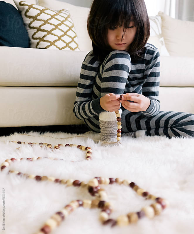 Young boy creates wooden bead garland by kelli kim for Stocksy United