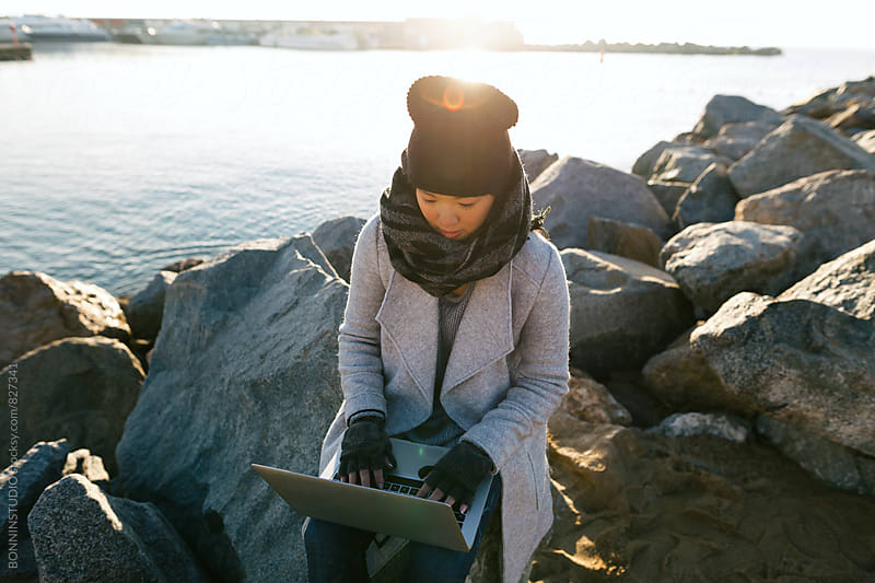 Asian woman using her laptop sitting on rock dock. by BONNINSTUDIO for Stocksy United