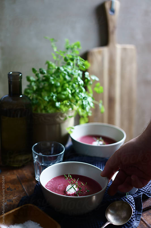 Beetroot soup: Hand taking a bowl of beetroot soup from a table. by Darren Muir for Stocksy United