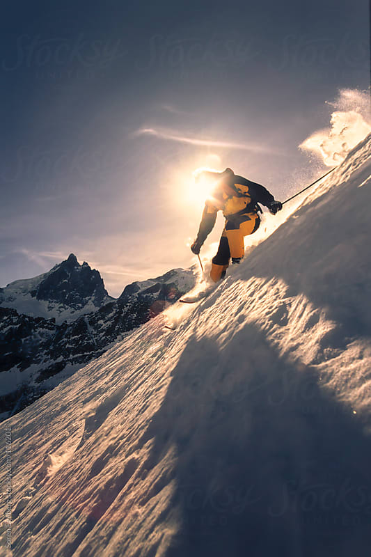 Mans skiing powder snow in winter mountains backlit by the sun by Soren Egeberg for Stocksy United
