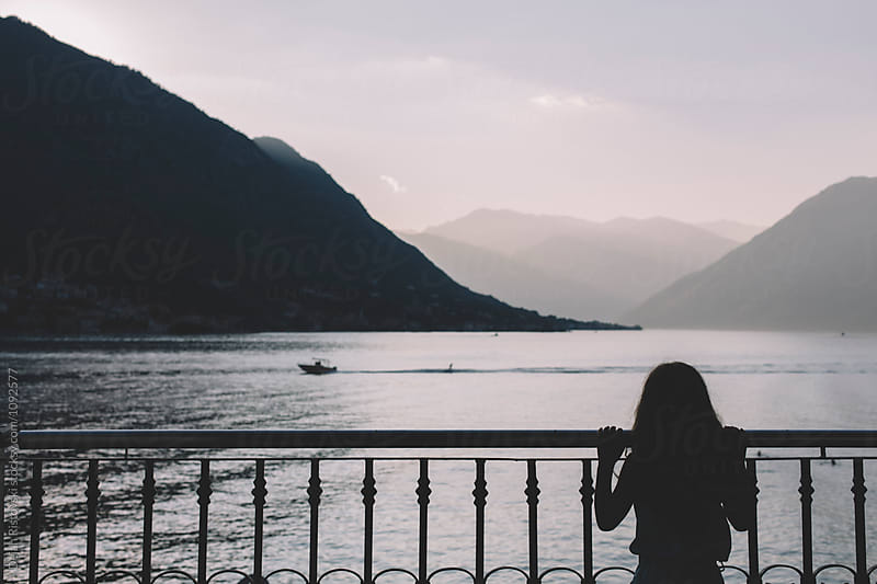 Girl looking at the sea from a terrace. by Dejan Ristovski for Stocksy United