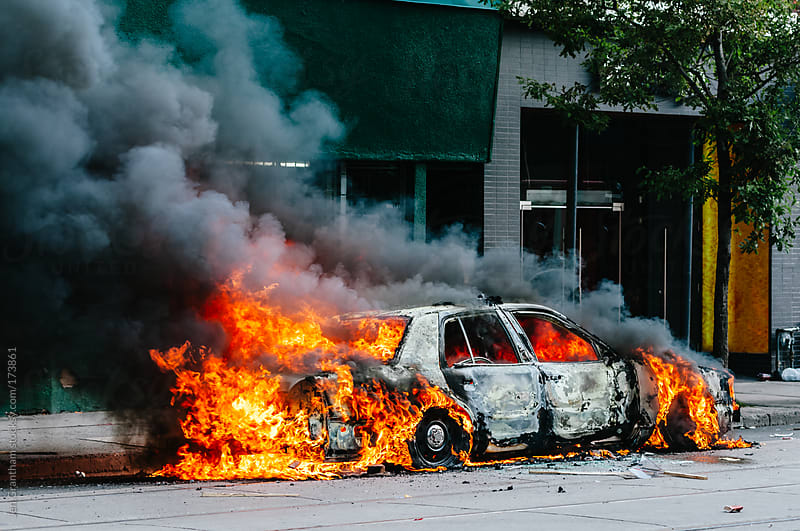 Burning police car by Jen Grantham for Stocksy United