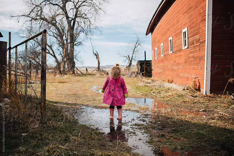 Toddler girl standing in puddle by Jessica Byrum for Stocksy United