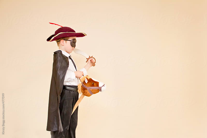 Boy in highwayman costume on hobby horse by Kirsty Begg for Stocksy United