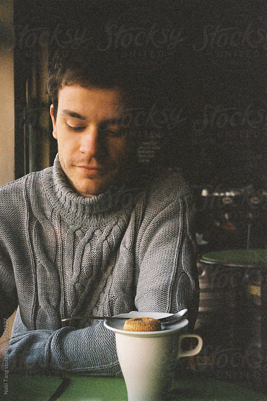 Image from analog camera of a young man in the cafe drinking tea by Nabi Tang for Stocksy United