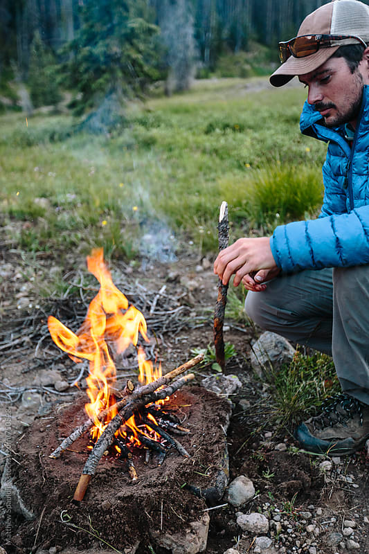 Man feeding sticks to small fire outdoors while camping by Matthew Spaulding for Stocksy United