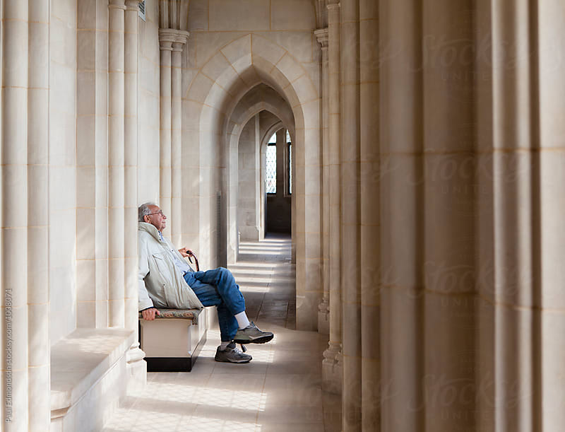 Senior man sitting and have quiet moment in cathedral by Paul Edmondson for Stocksy United