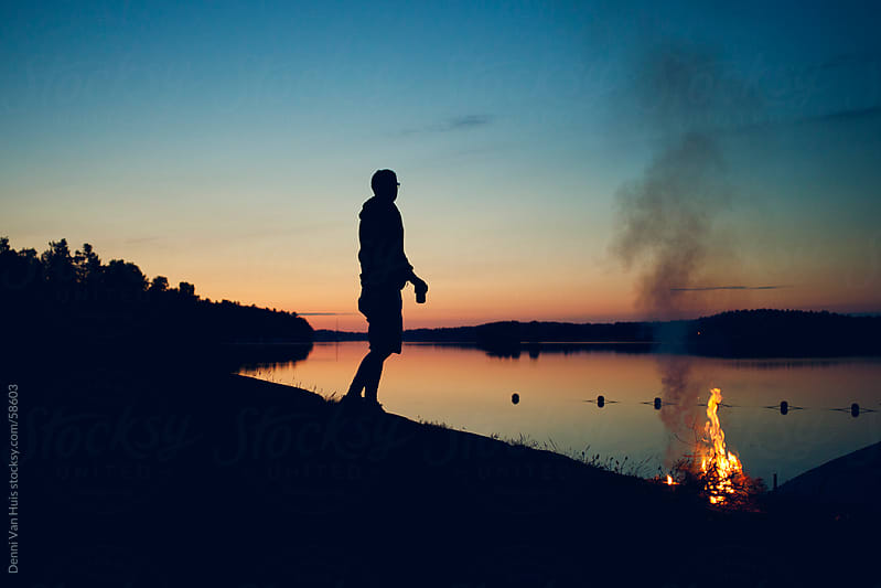 Young man making a campfire right next to a lake on a summer night by Denni Van Huis for Stocksy United