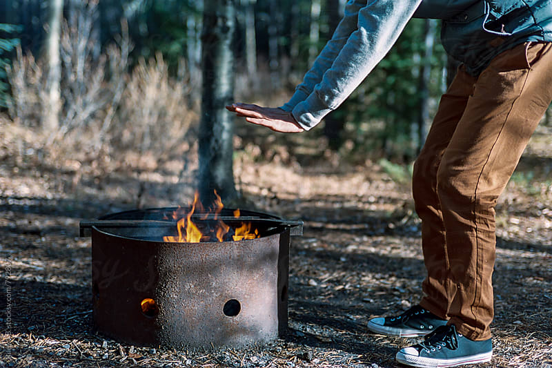 A man warms his hands over a fire in a camping fire pit. by Riley J.B. for Stocksy United