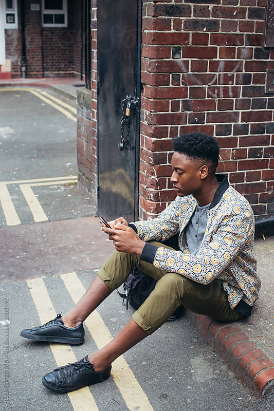 Young Fashionable Black Man Using Cellphone on London Sidewalk by Julien L. Balmer for Stocksy United