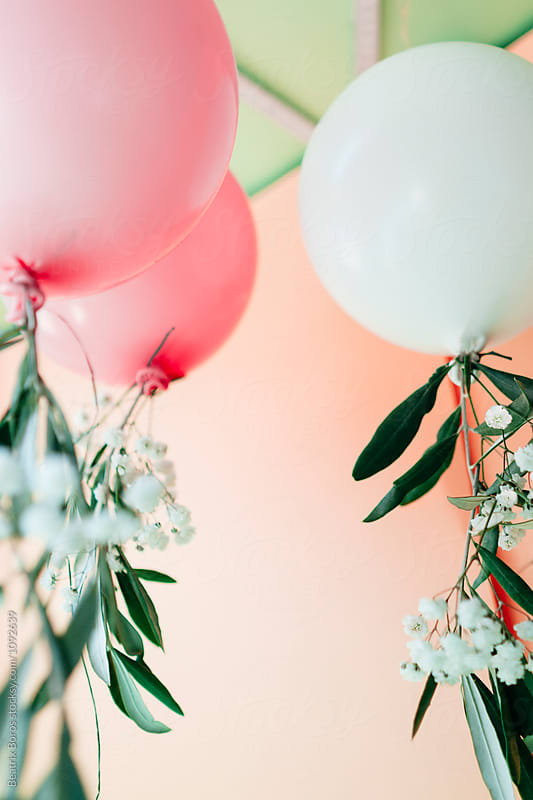 Balloons decorated with flowers and leafs by the ceiling of a room by Beatrix Boros for Stocksy United