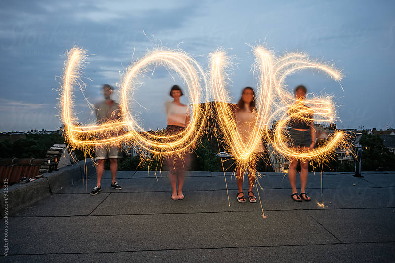 Four people writing the word 'love' with sparklers. by VegterFoto for Stocksy United