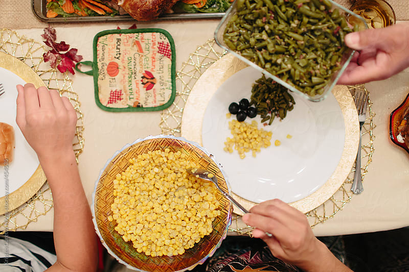 Passing around Thanksgiving sides at the dinner table by Kristen Curette Hines for Stocksy United