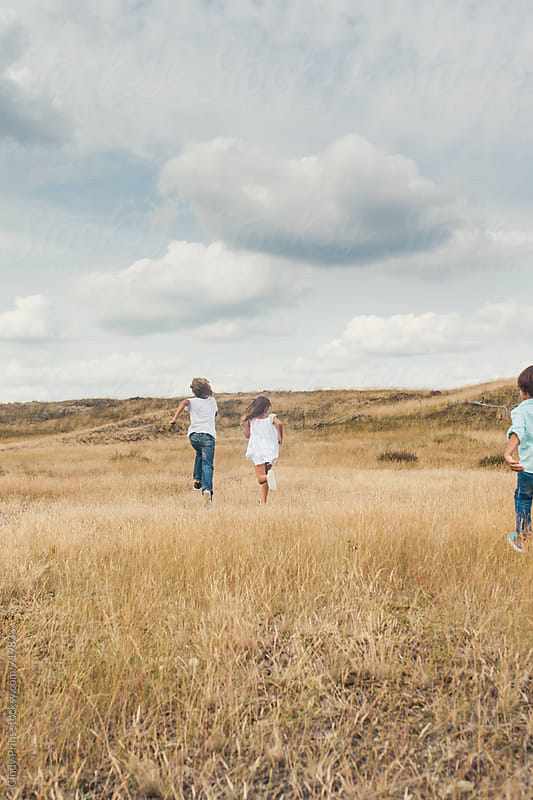 Back view of kids running in a golden field on a cloudy summer day by Cindy Prins for Stocksy United