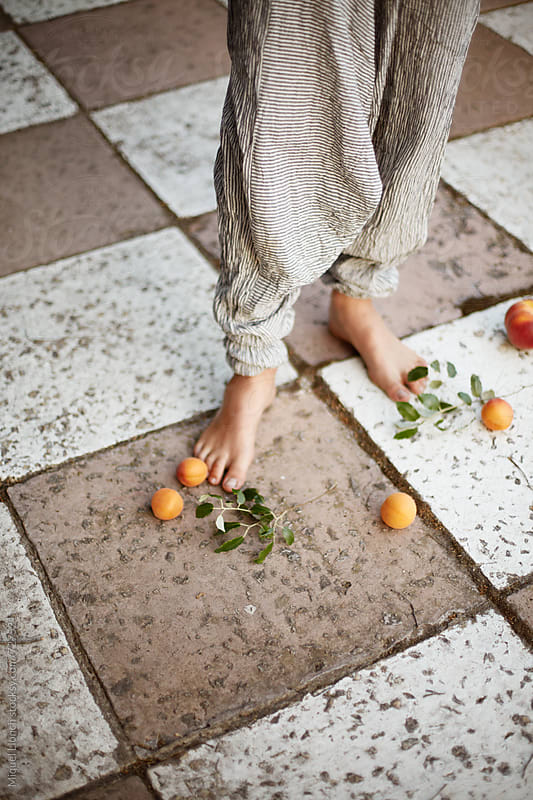 Fruit and feet on the ground with nice pants by Miquel Llonch for Stocksy United