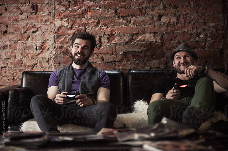 Two male friends gaming together by Milles Studio for Stocksy United