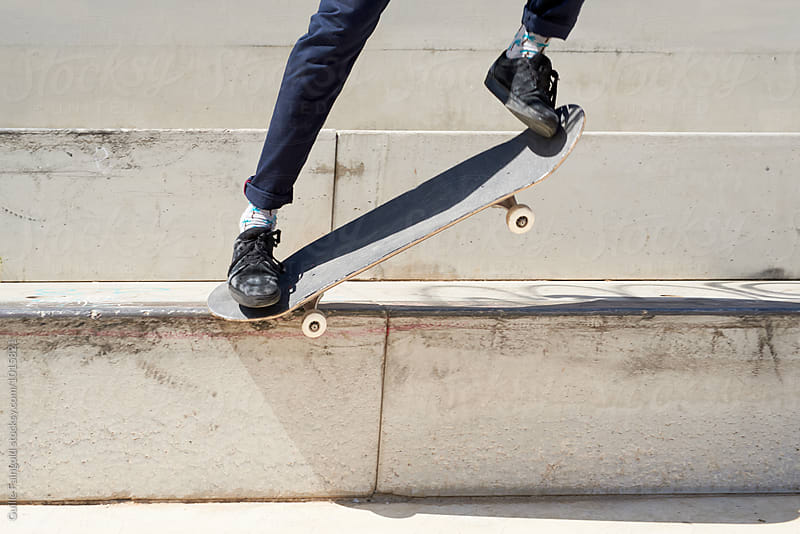 Close-up of man doing trick on skateboard by Guille Faingold for Stocksy United