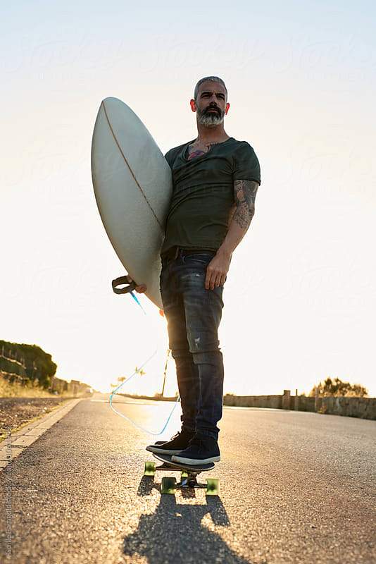 Handsome longboarder carrying surfboard along road by Guille Faingold for Stocksy United