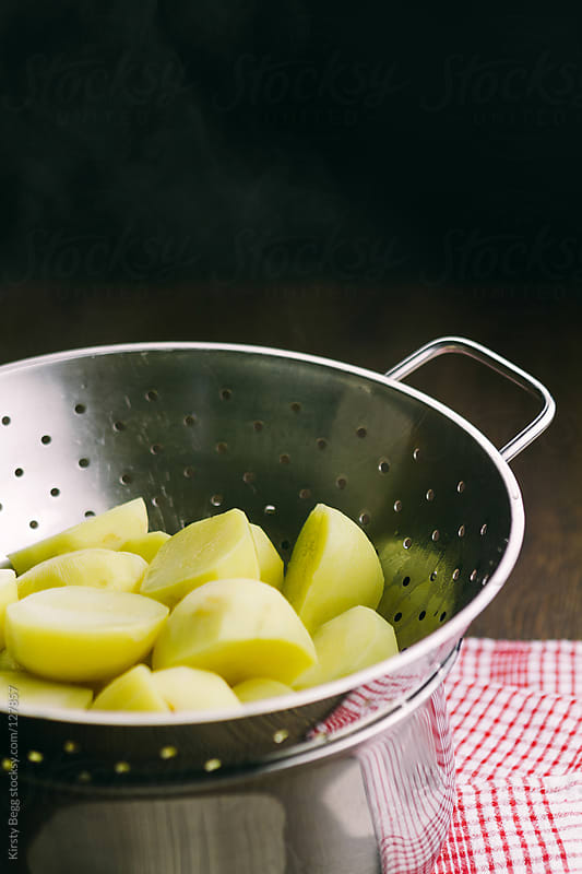 Boiled potatoes steaming in a colander by Kirsty Begg for Stocksy United