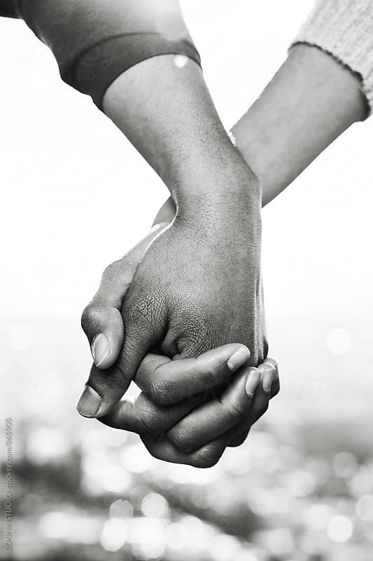 Closeup of couple holding hands outside. Black and white photo. by BONNINSTUDIO for Stocksy United