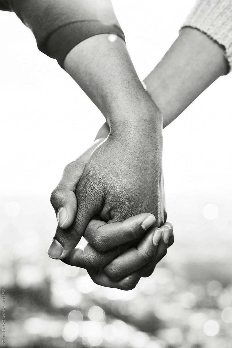 Closeup of couple holding hands outside black and white photo by bonninstudio for stocksy