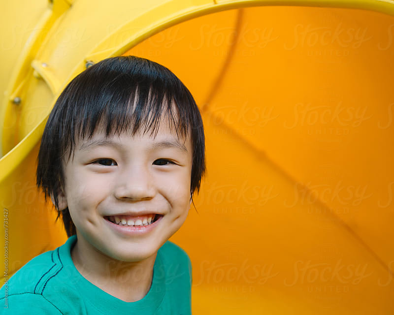A young kid is all smiles for the camera after sliding down the tube slide by Lawrence del Mundo for Stocksy United