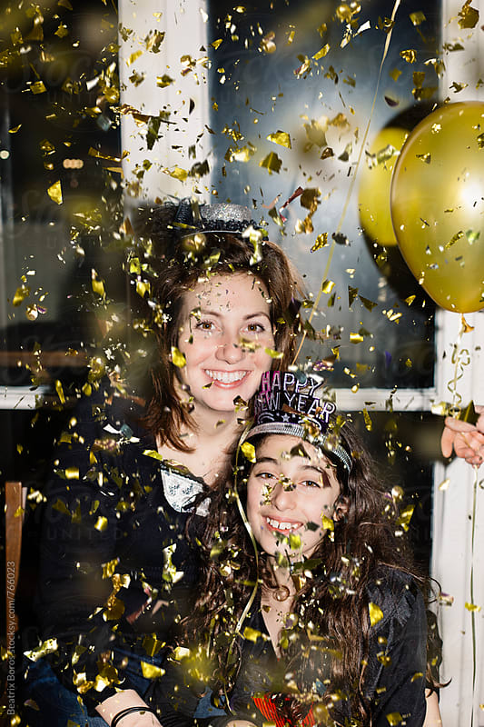 Woman and preteenager girl happily looking at camera while confetti is falling by Beatrix Boros for Stocksy United