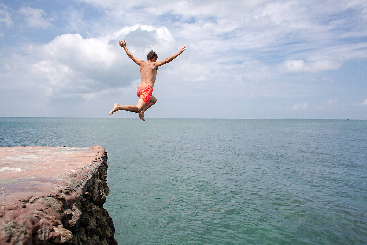 Summer fun - man jumping off cliff into the ocean by Jovo ...