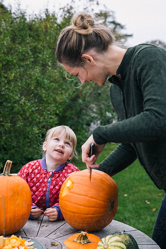 Mother and daughter carve pumpkins in garden for halloween by Lior + Lone for Stocksy United