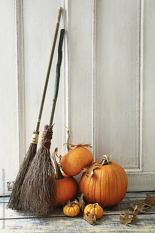 Brooms and pumpkins in front of door by Sandra Cunningham for Stocksy United