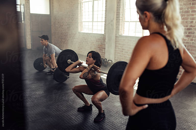 Woman lifts barbell with personal trainer by Jacob Lund for Stocksy United
