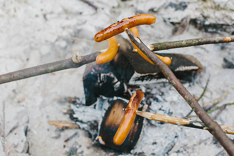 Tasty smoked sausages grilling on an open fire by Amir Kaljikovic for Stocksy United