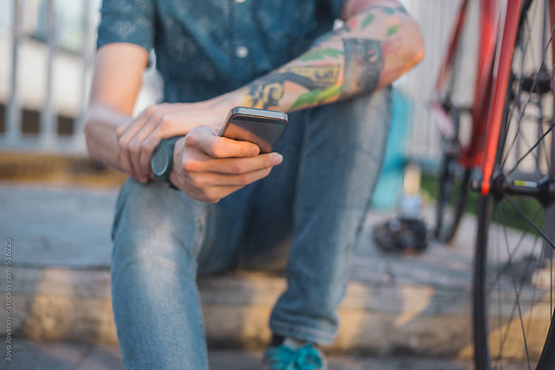 Young tattooed man checking his phone by Jovo Jovanovic for Stocksy United