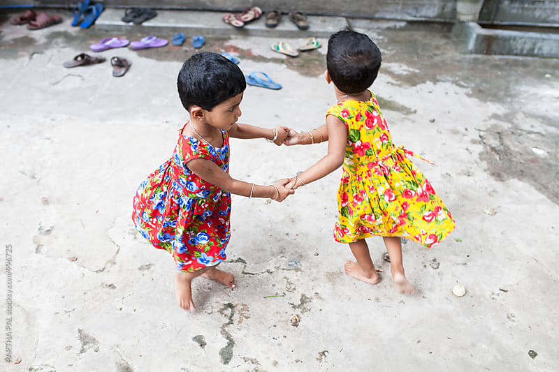 Twin girls  holding hands and playing together by PARTHA PAL for Stocksy United