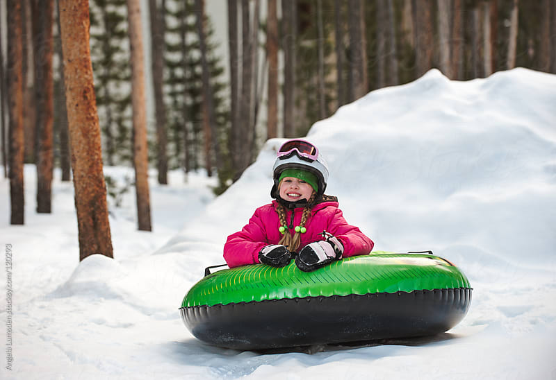 Girl smiling after a fun toboggan ride by Angela Lumsden for Stocksy United