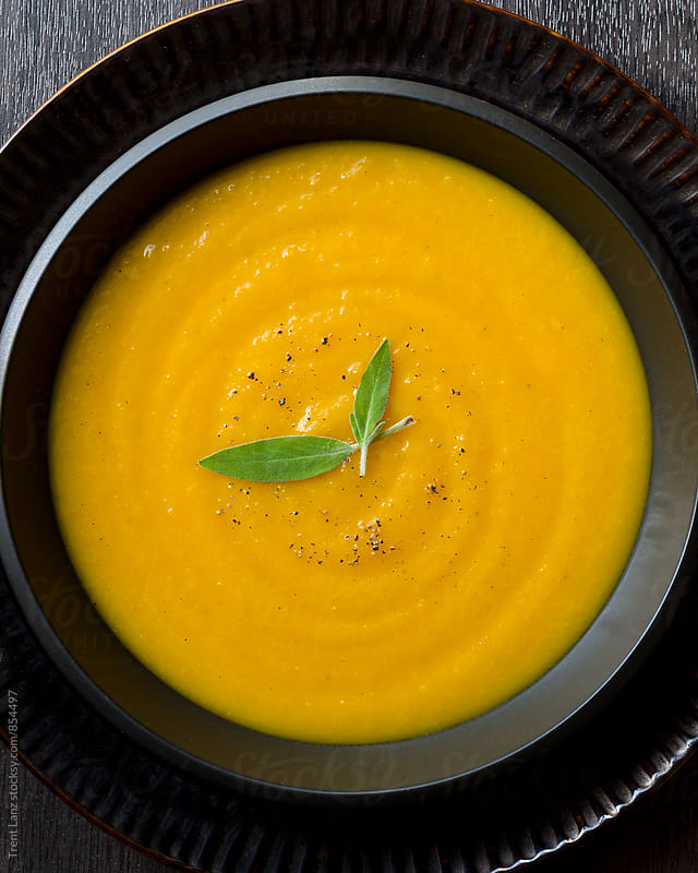 Delicious butternut pumpkin bisque cream soup by Trent Lanz for Stocksy United