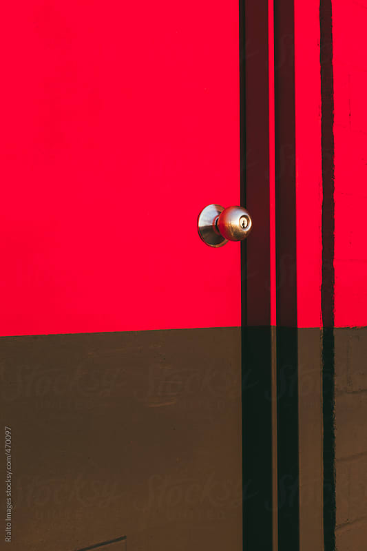 Brightly colored red and brown door on building exterior by Paul Edmondson for Stocksy United