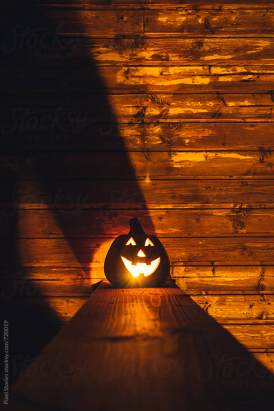Ceramic pumpkin with lit candle on porch by Pixel Stories for Stocksy United