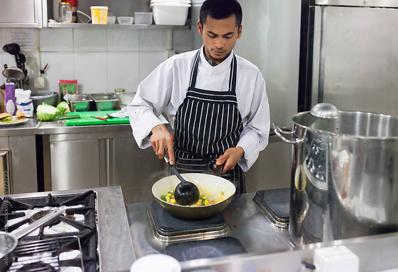 Young indonesian cook prepares a meal in a restaurant kitchen by Jelena Jojic Tomic for Stocksy United