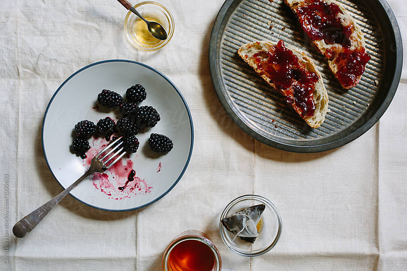 Breakfast of toast and jam, tea, honey, and blackberries by Christine Han for Stocksy United