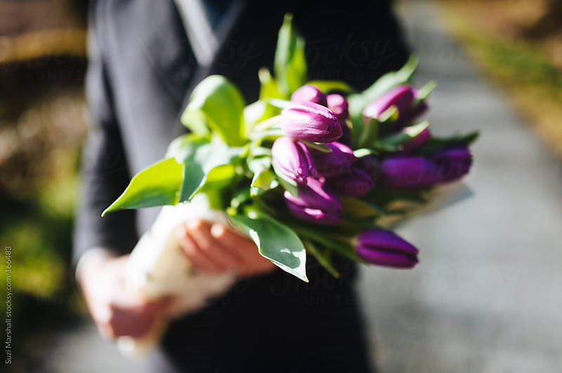 Man holding bunch of flowers by Suzi Marshall for Stocksy United