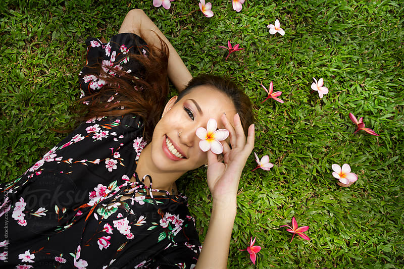 Asian woman lying in the grass by Felix Hug for Stocksy United