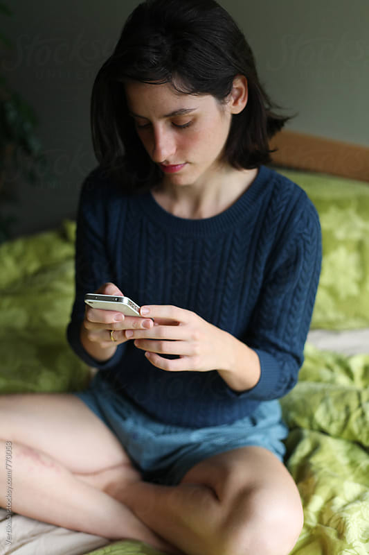 Beautiful younger woman using her cell phone  by Marija Mandic for Stocksy United