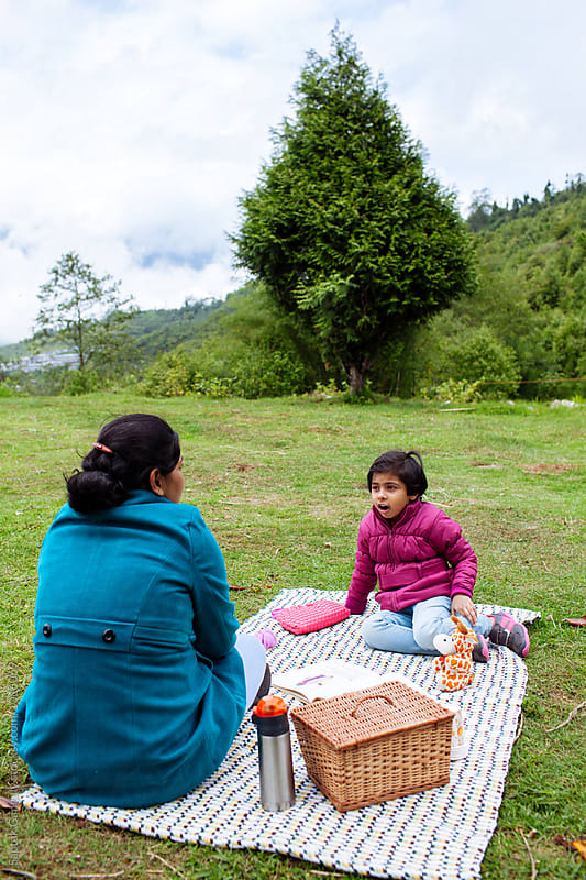 Mother and daughter enjoying a picnic in the hills by Saptak Ganguly for Stocksy United