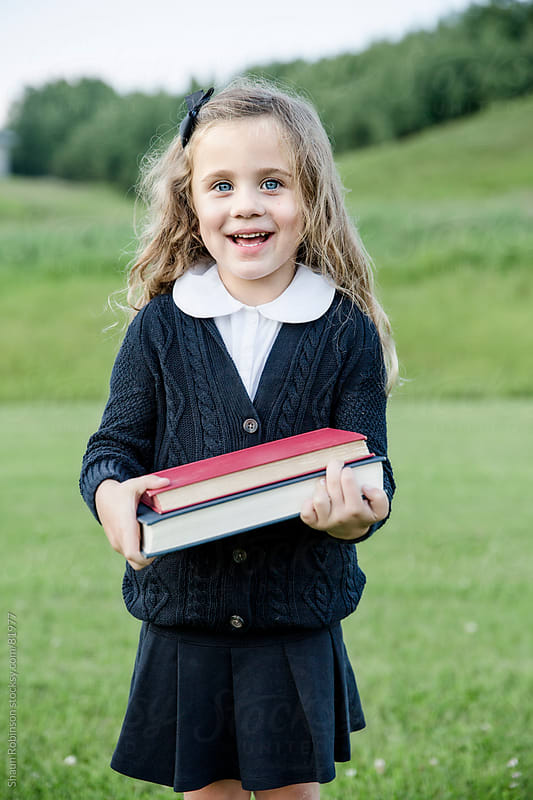 portrait of school girl standing in a field with two books by Shaun Robinson for Stocksy United
