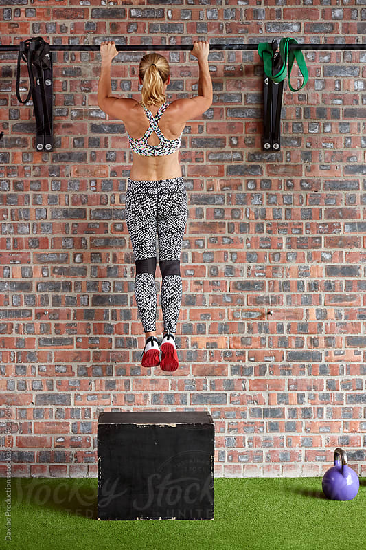 Young sporty woman doing body pull-ups in a gym by Daxiao Productions for Stocksy United