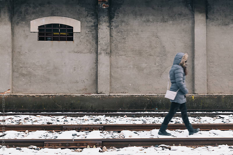 Woman Walking Through a Railway by VICTOR TORRES for Stocksy United