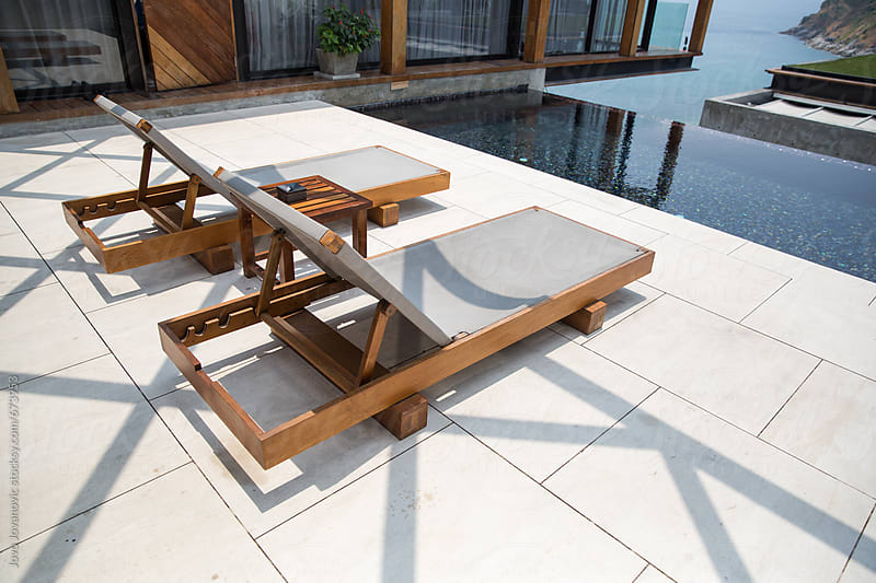 Two outdoor lounge chairs next to a luxurious swimming pool by Jovo Jovanovic for Stocksy United
