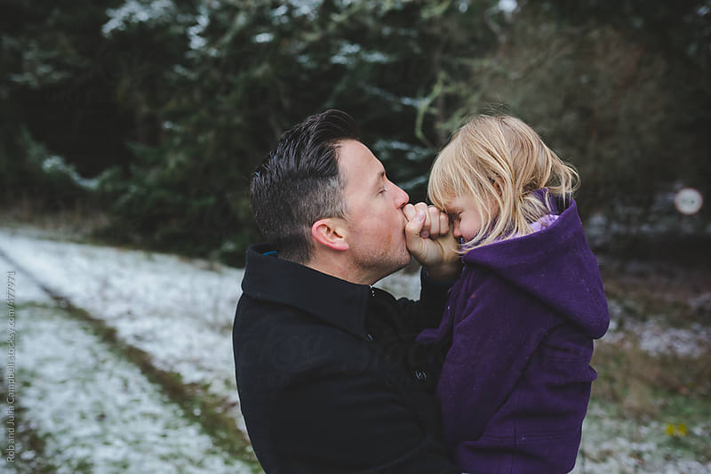 Dad warms up daughters nose on cold winter day by Rob and Julia Campbell for Stocksy United
